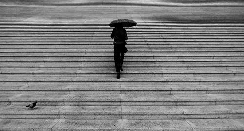 Grayscale Photography of Woman Walking Upstairs