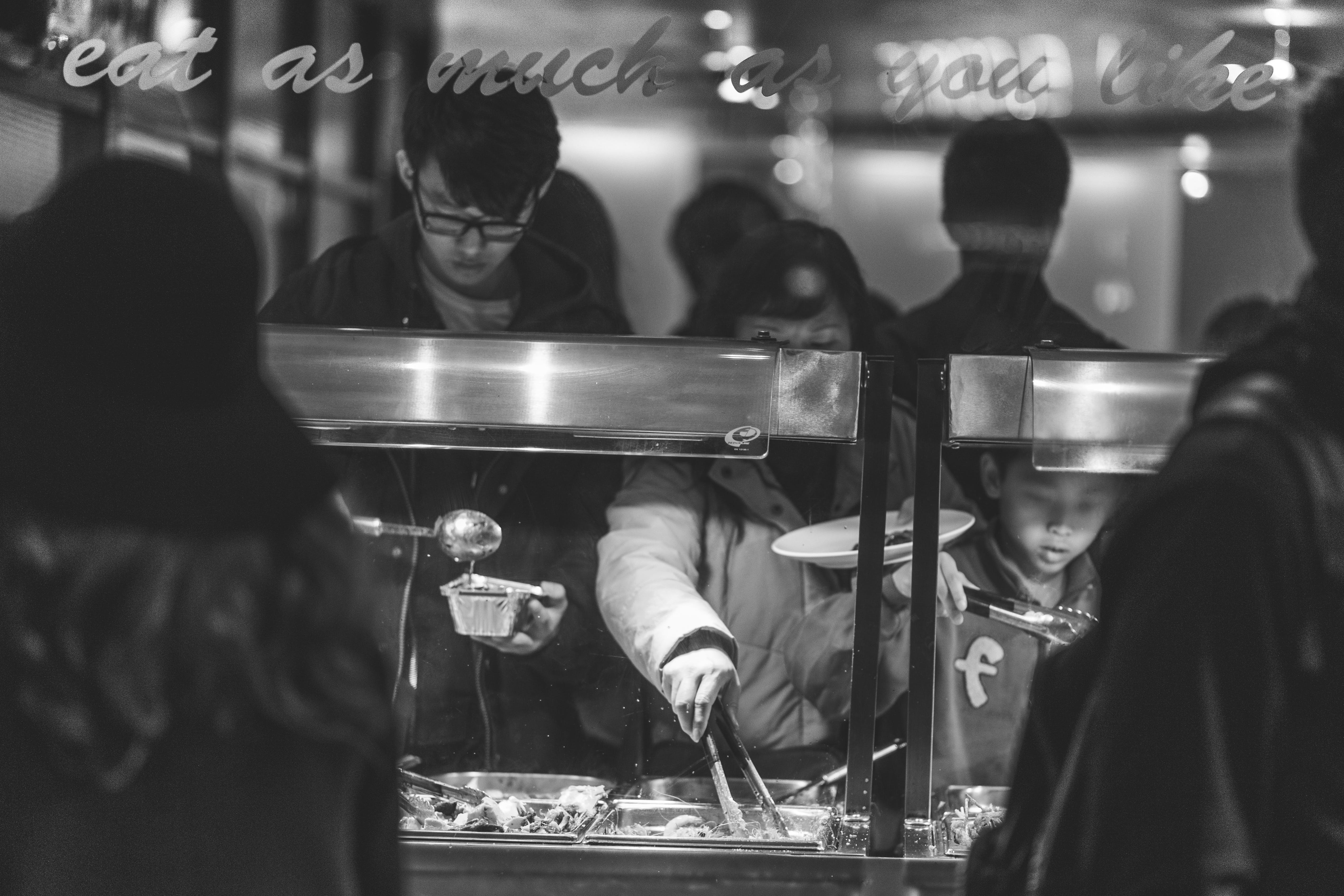 Grayscale Photo of Children Taking Food from Counter