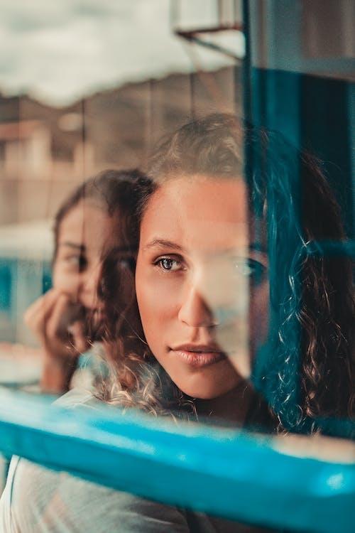 Woman Sitting Beside Glass Window