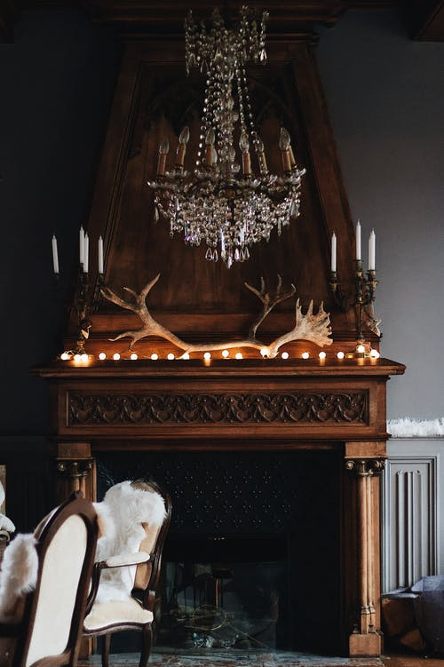 Brown wooden fireplace with antler decor and old fashioned candlesticks on mantelpiece in cozy room with elegant chandelier and fur covered chairs