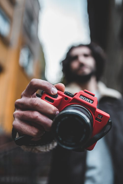 Shallow Focus Photography of Man Holding Red Sony Camera