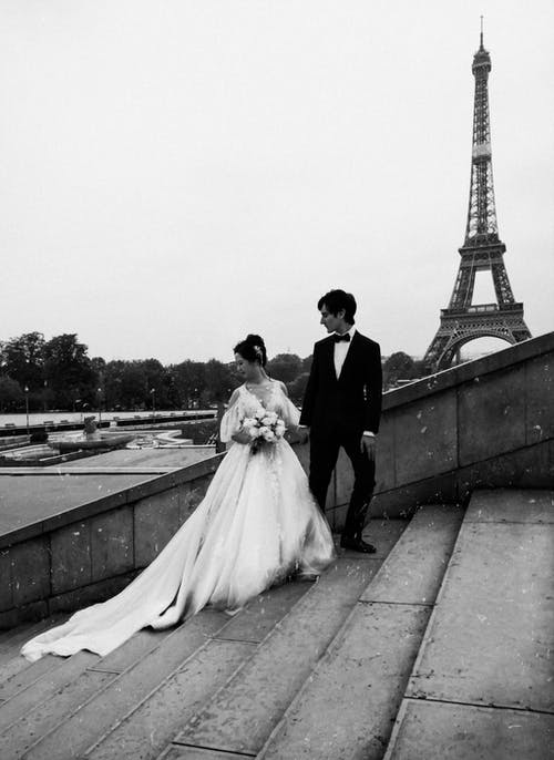 Grayscale Photo of Bride and Groom Standing on Concrete Stairs