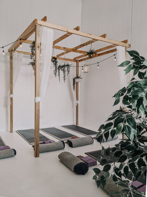 Brown Wooden Framed Canopy Above Yoga mat