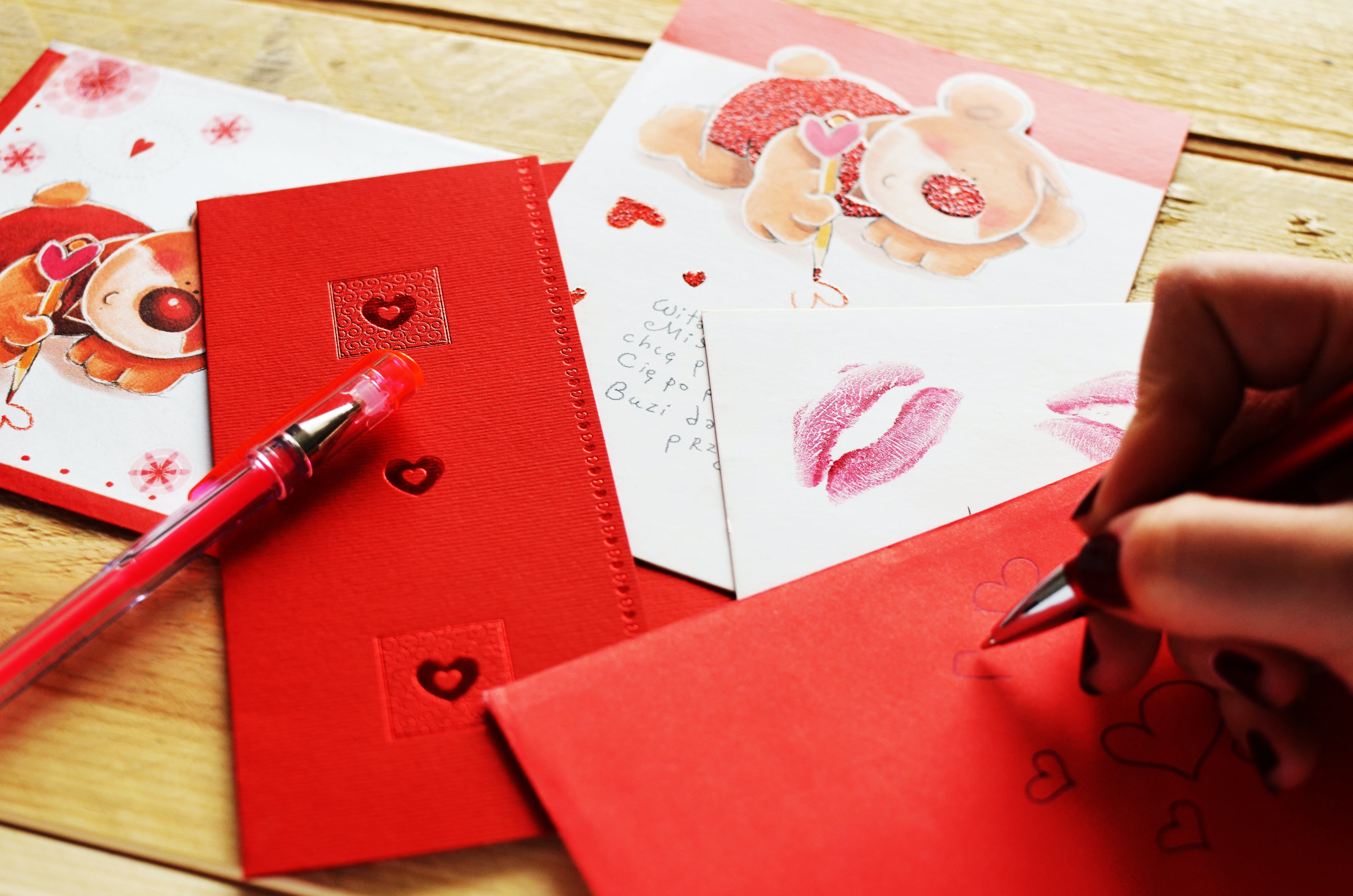 Person Holding Pen While Writing a Heart