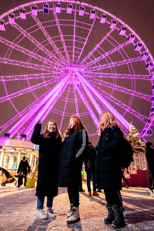 Photo of Three Women Standing Against Ferris Wheel