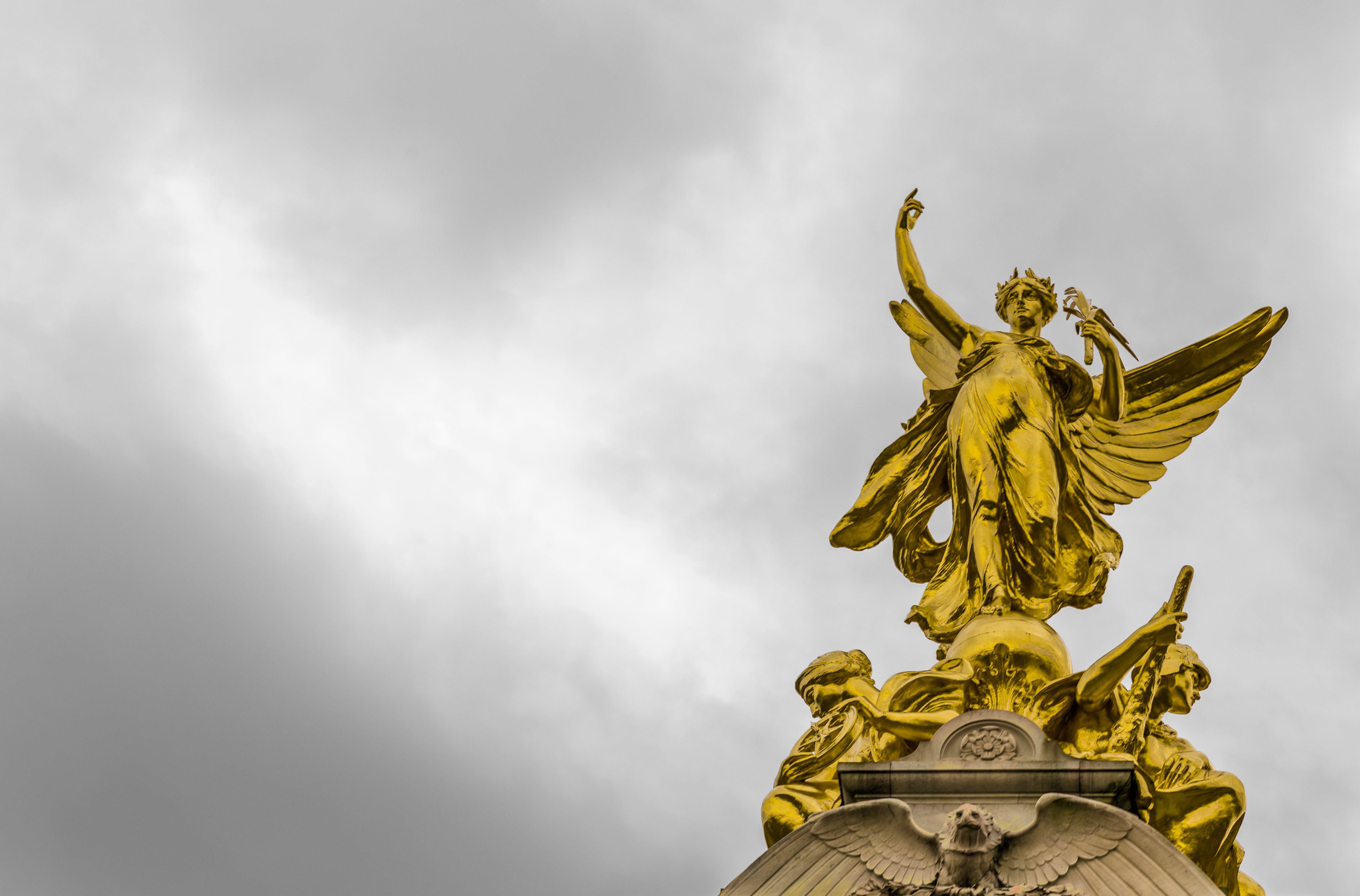 Gold Angel Statue Under Grey Clouds