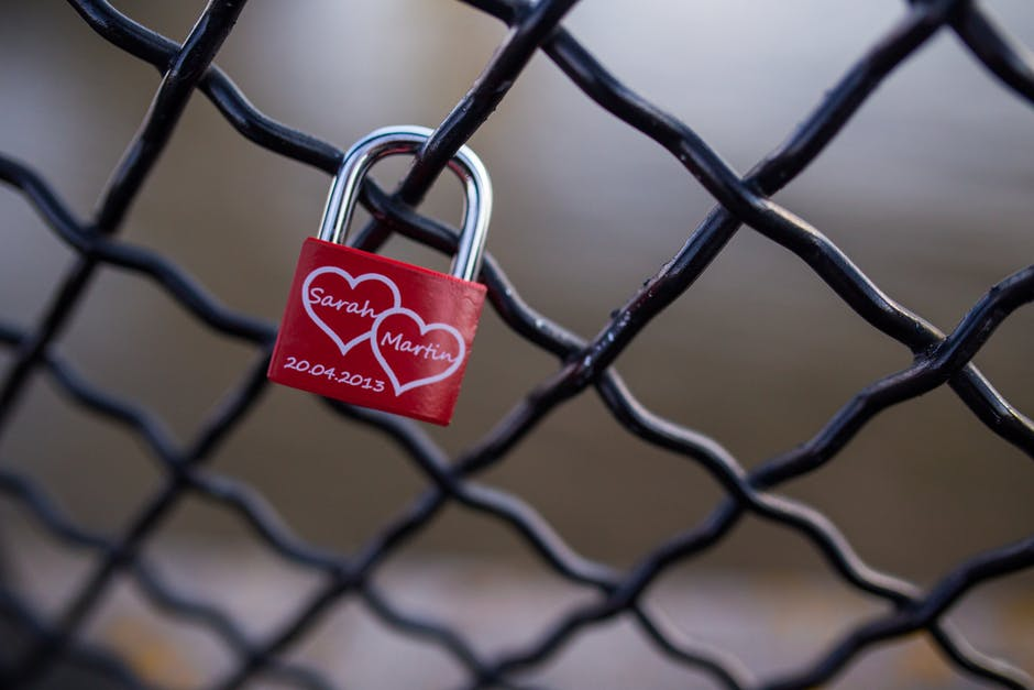Red and Stainless Steel 2 Hearts Padlock on Black Cyclone Fence during Daytime