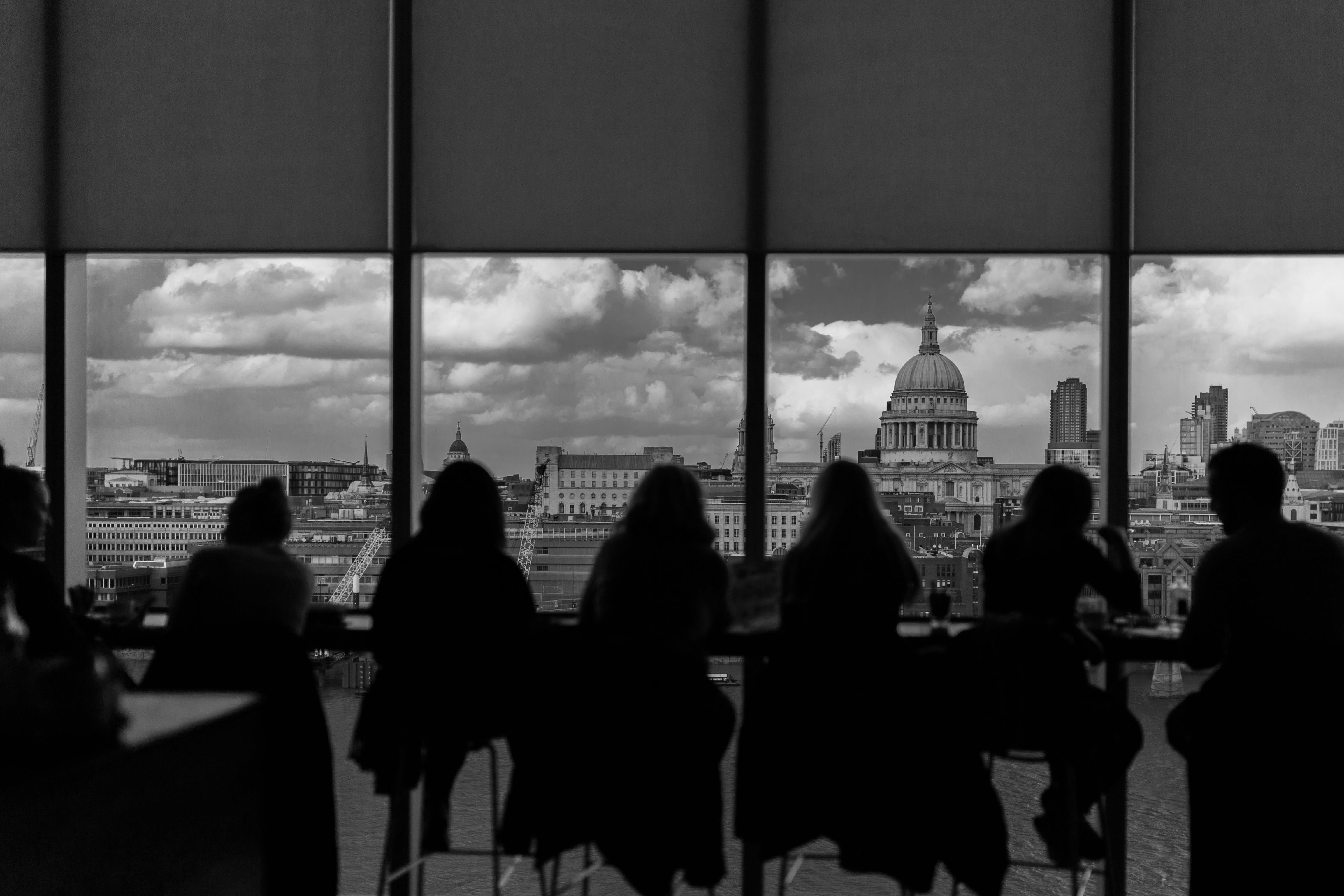 Greyscale Photography of Silhouette of People Inside Building