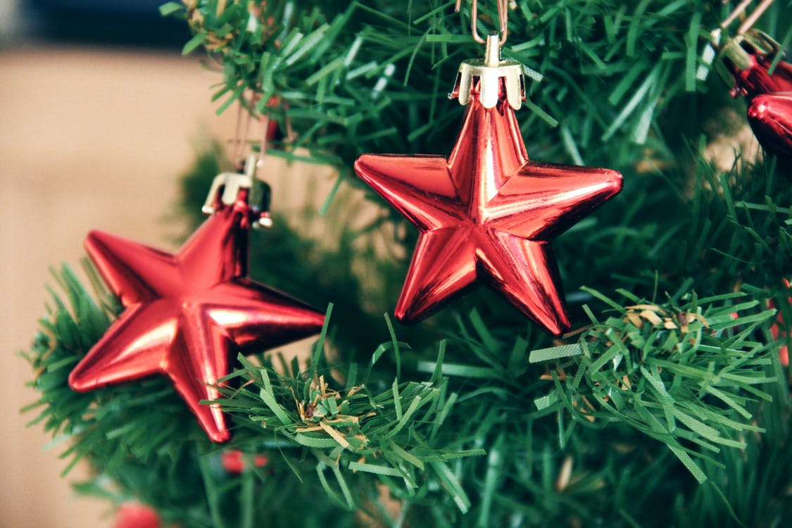 Two Red Star Baubles on Green Christmas Tree