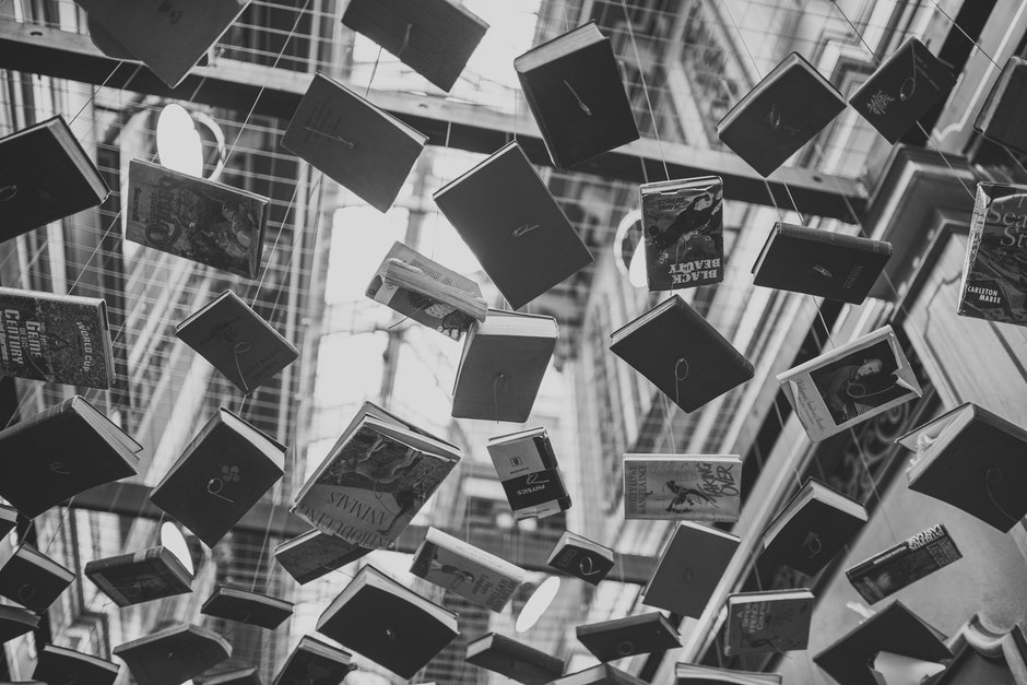 Grayscale Photo of Hanging Books