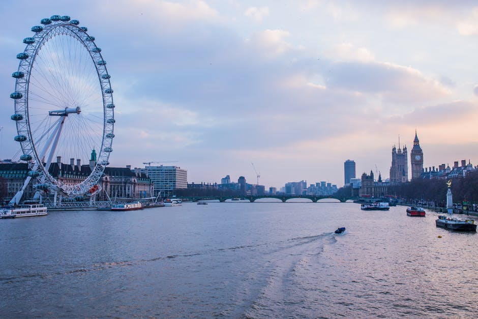 daytime view of the river thames and london eye with westminster palace in the background