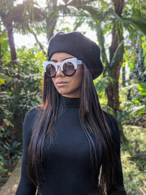 Woman Wearing a Cap and Sunglasses
