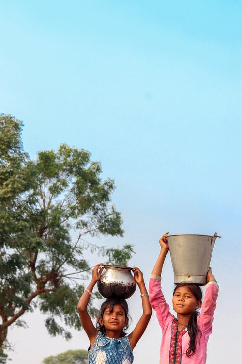 Two Girls Carrying Buckets