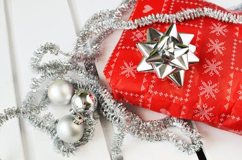 Several Silver Bauble Balls Beside Red Wrapper