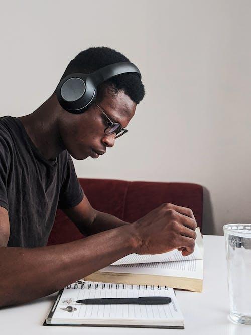 앉아있는 동안 책을 읽고 검은 헤드폰을 사용하여 검은 색 크루 넥 티셔츠를 입은 남자