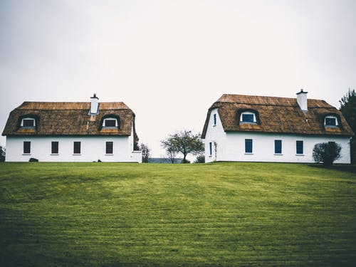 Two Houses With Green Grass
