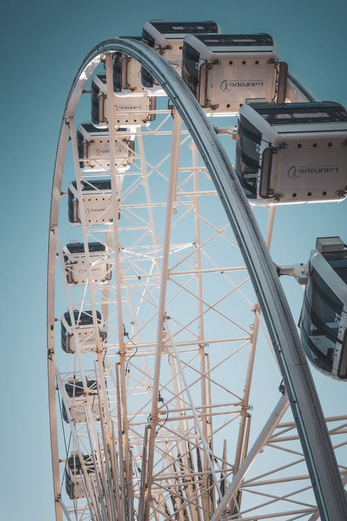 From below of contemporary Ferris wheel with white cabins in city amusement park in bright sunny day