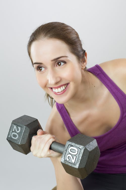 Woman Wearing Purple Tank Top Holding Dumbbells at 20kg