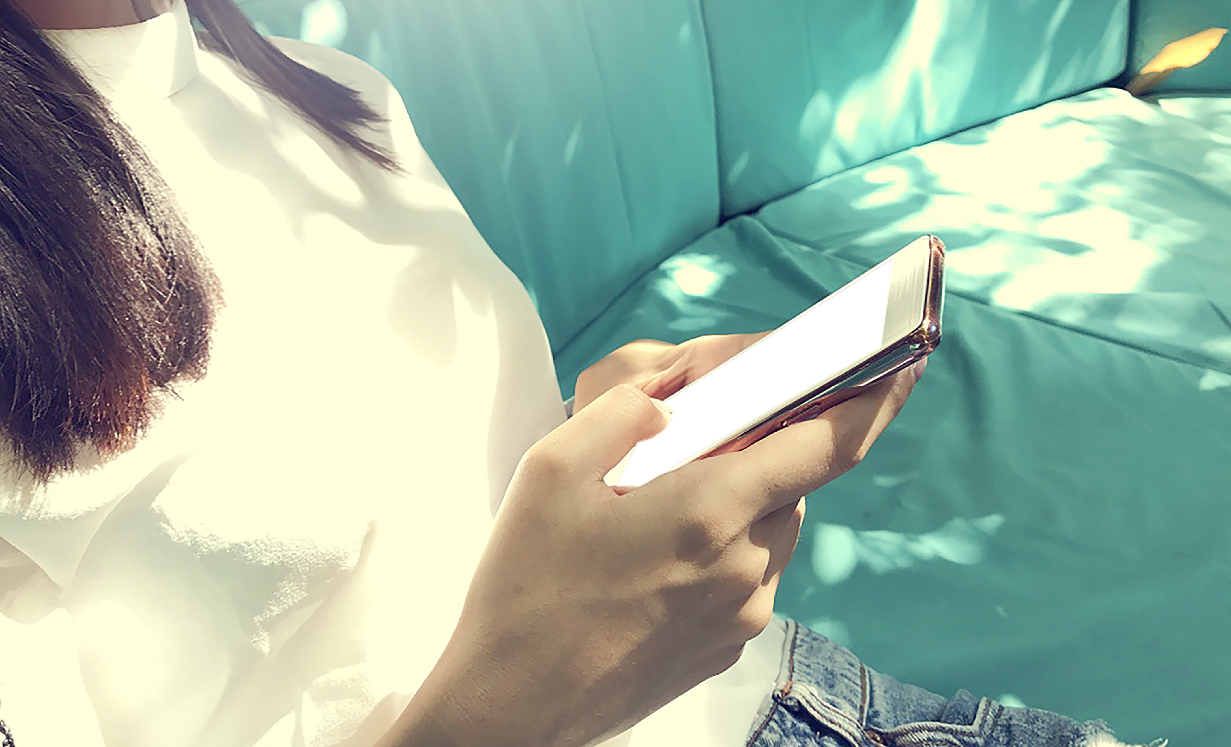 Woman Wearing White Top Holding Black Smartphone