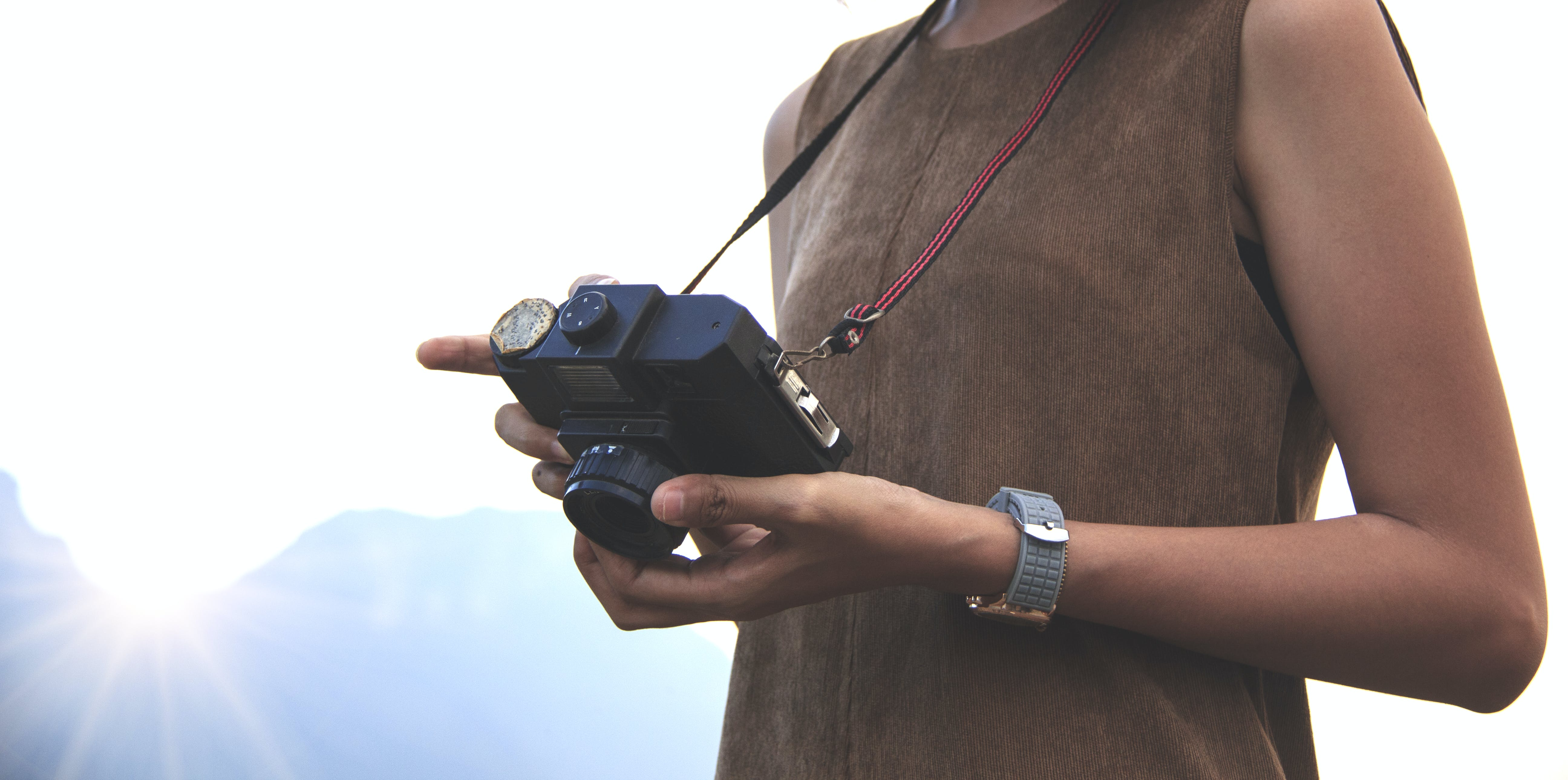 Woman Holding Camera Near Mountain