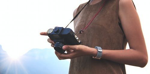 Woman Holding Camera Near Mountain