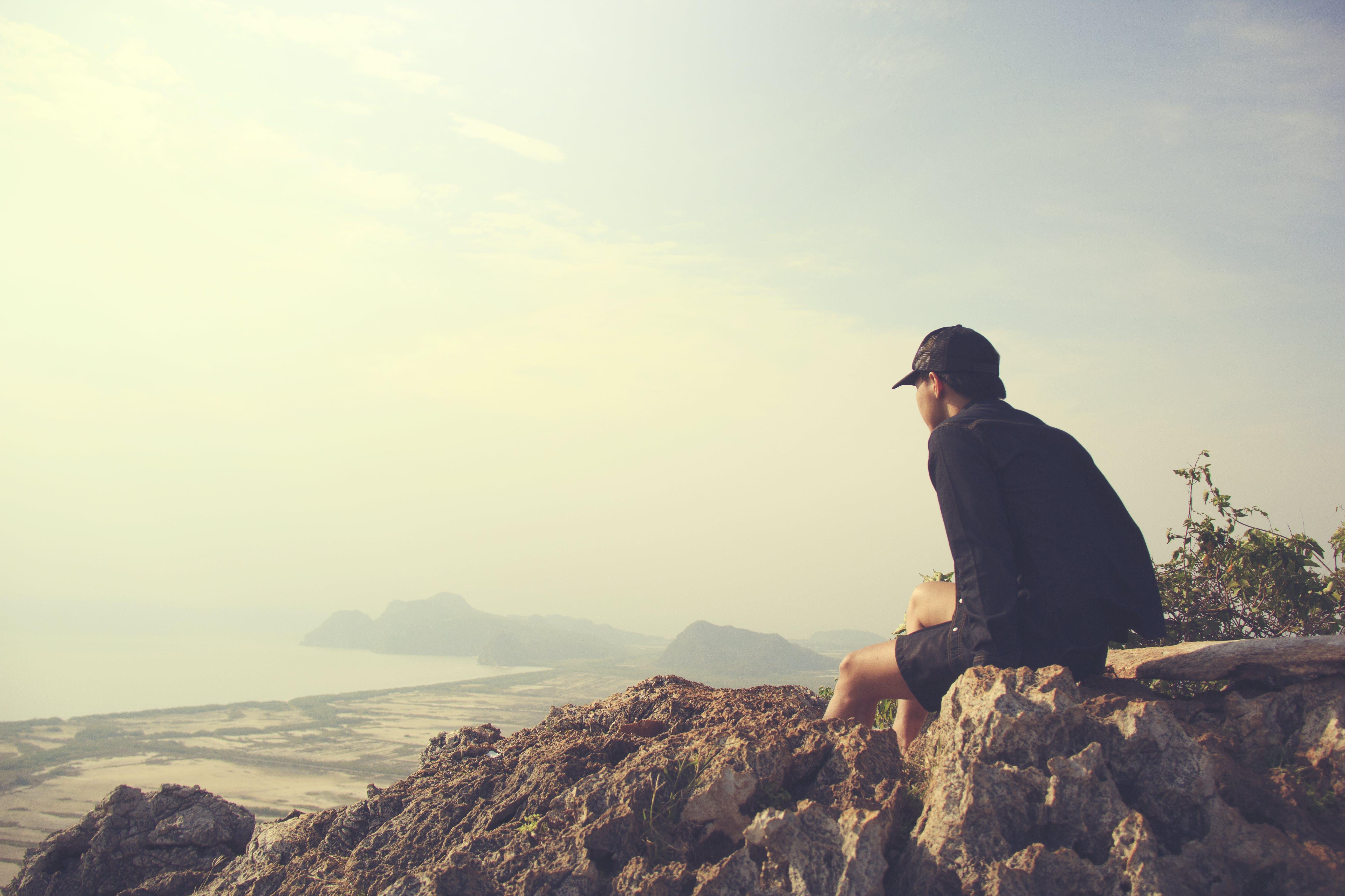 Man Sitting on Brown Rocks Facing Seashore