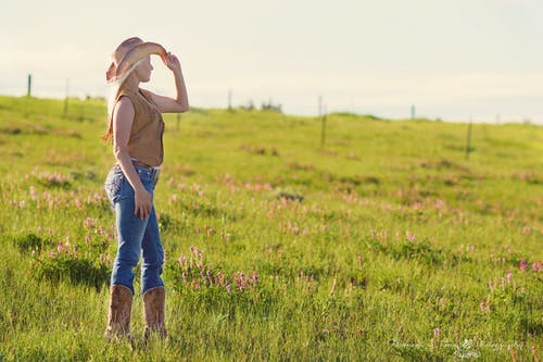 Woman Wearing Brown Cowboy Boots and Vest With Hat Under Blue Sky during Daytime