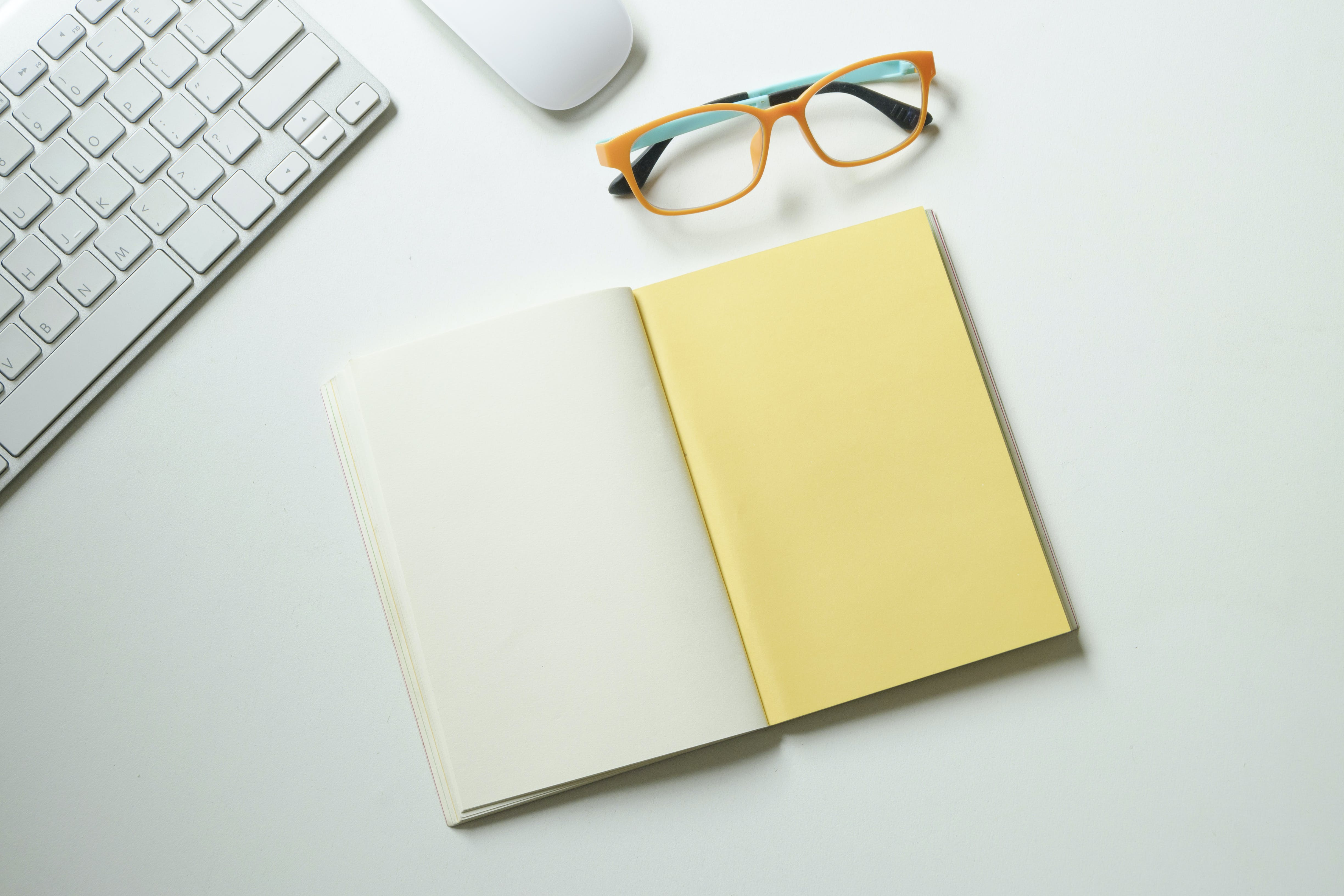 White and Yellow Notebook Placed Near Keyboard and Eyeglasses