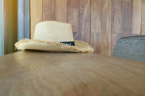 Beige and Black Straw Hat on Wooden Surface