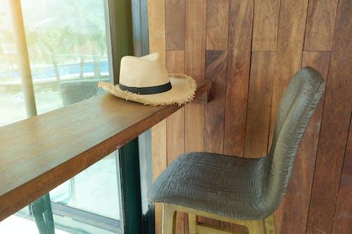 Foto profissional grátis de cadeira, cátedra, chapéu, cômodo