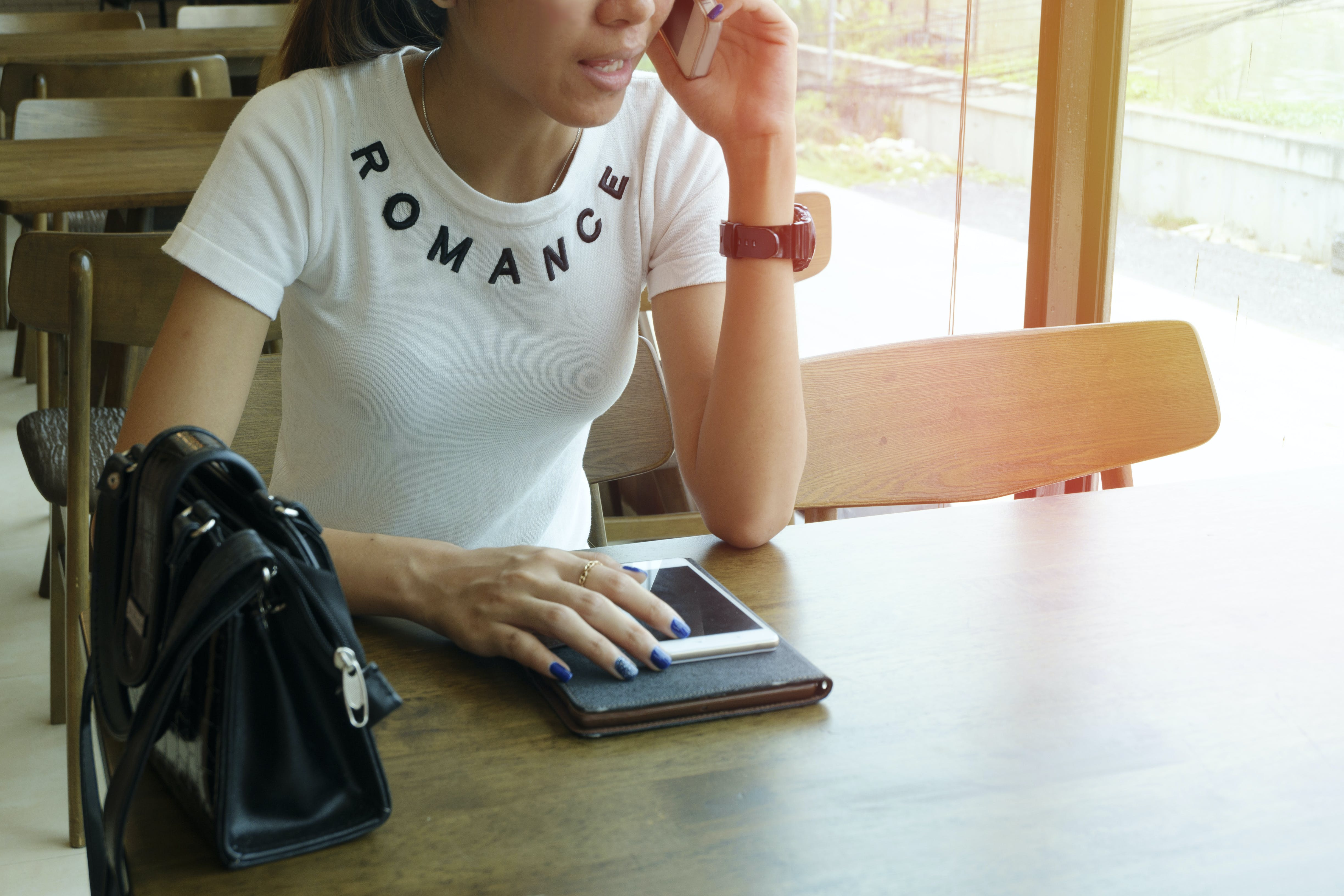 Woman Wearing White Romance-printed Crew-neck T-shirt While Sitting on Brown Wooden Chair