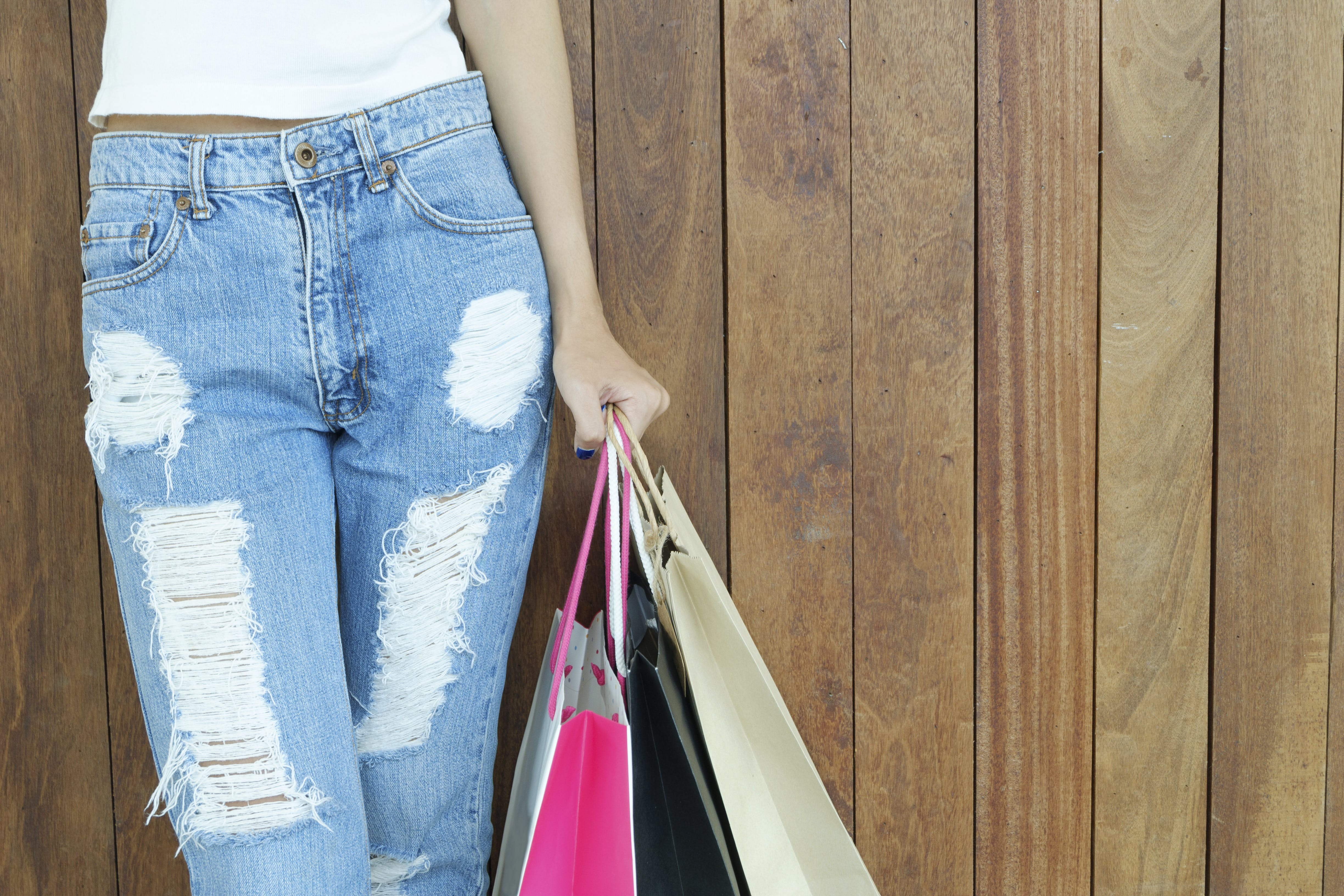 Woman Wearing Distressed Blue Jeans Holding Paper Bags
