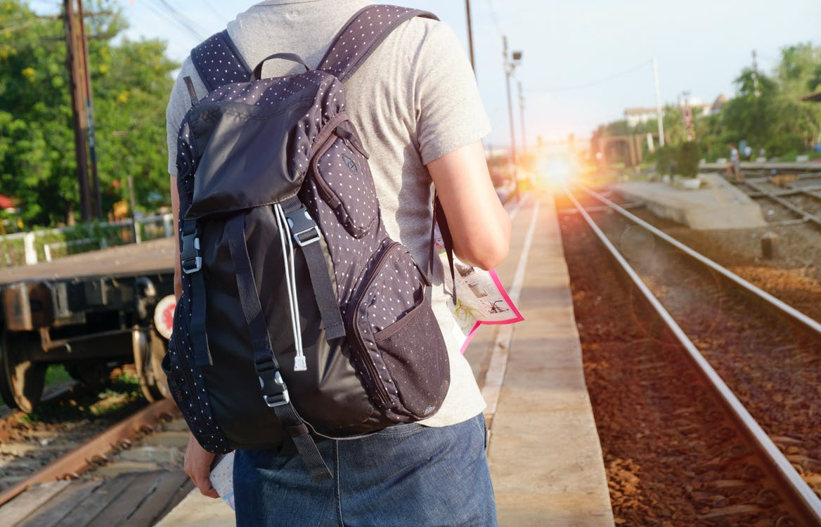 Person in Grey Top With Backpack Waiting for Train
