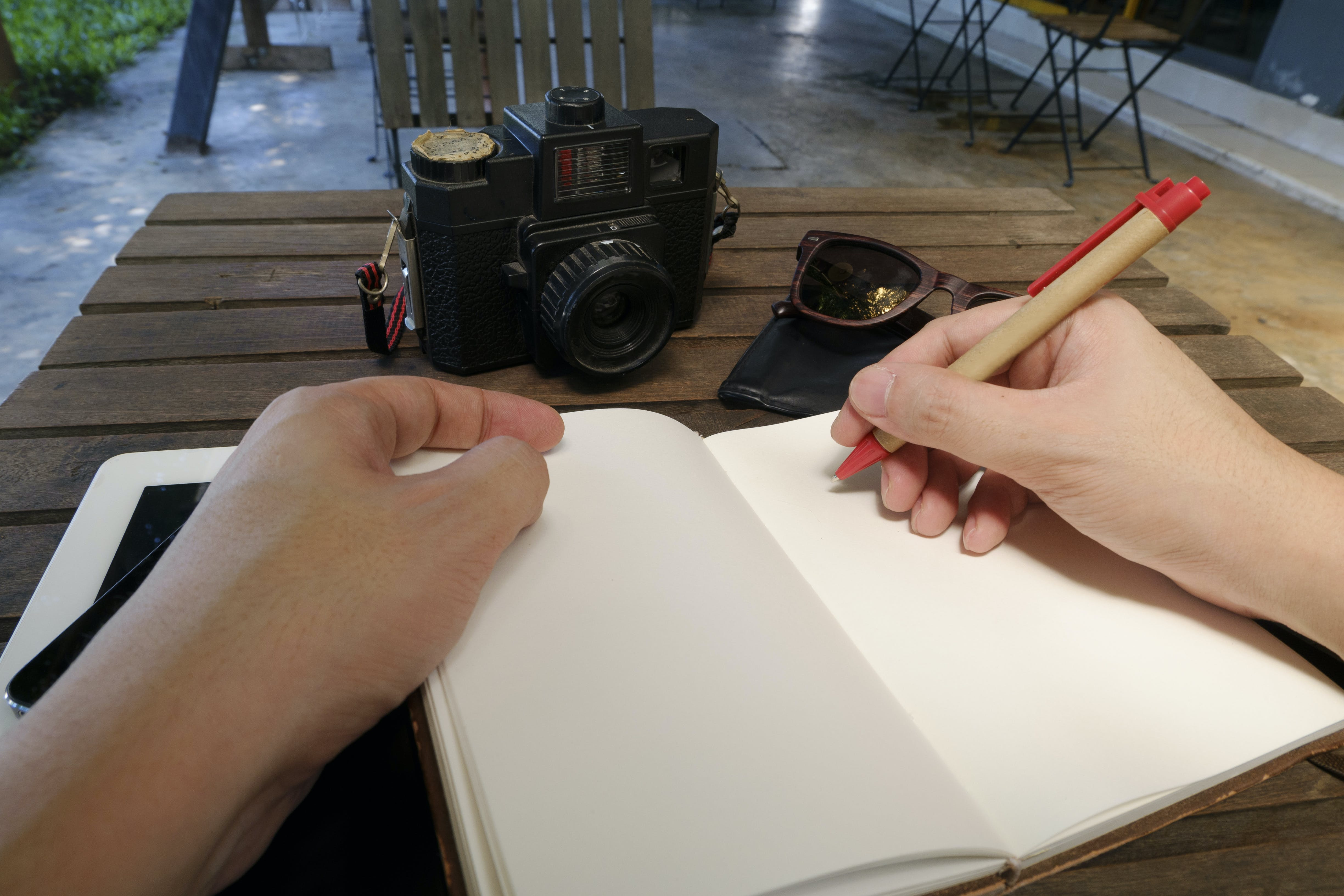 Person Writing Beside Dslr Camera on Brown Wooden Table