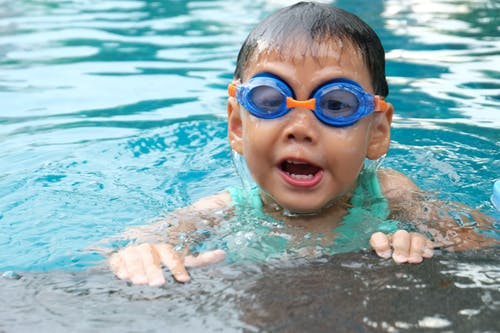 Toddler Swimming on Pool Wearing Blue Goggles