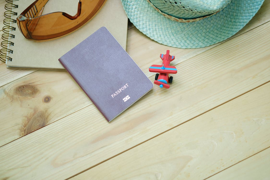 Gray Passport on Brown Board Beside Red Plane Toy