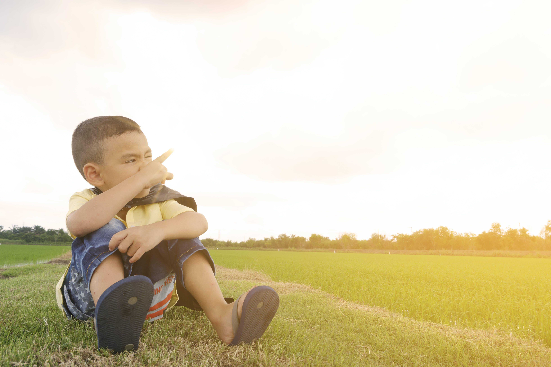 Boy Sits on Grass