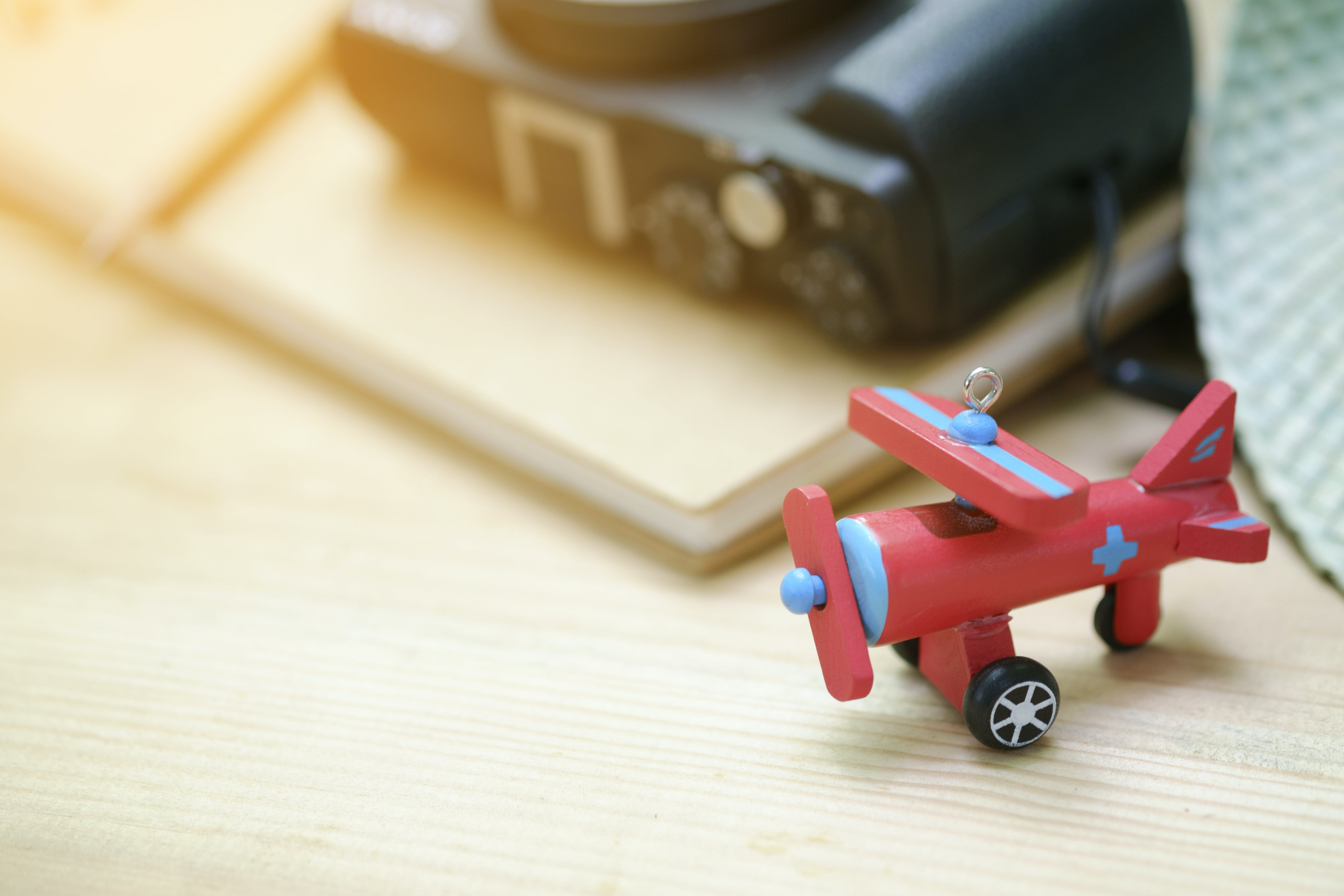 Red Biplane Toy on Wooden Surface