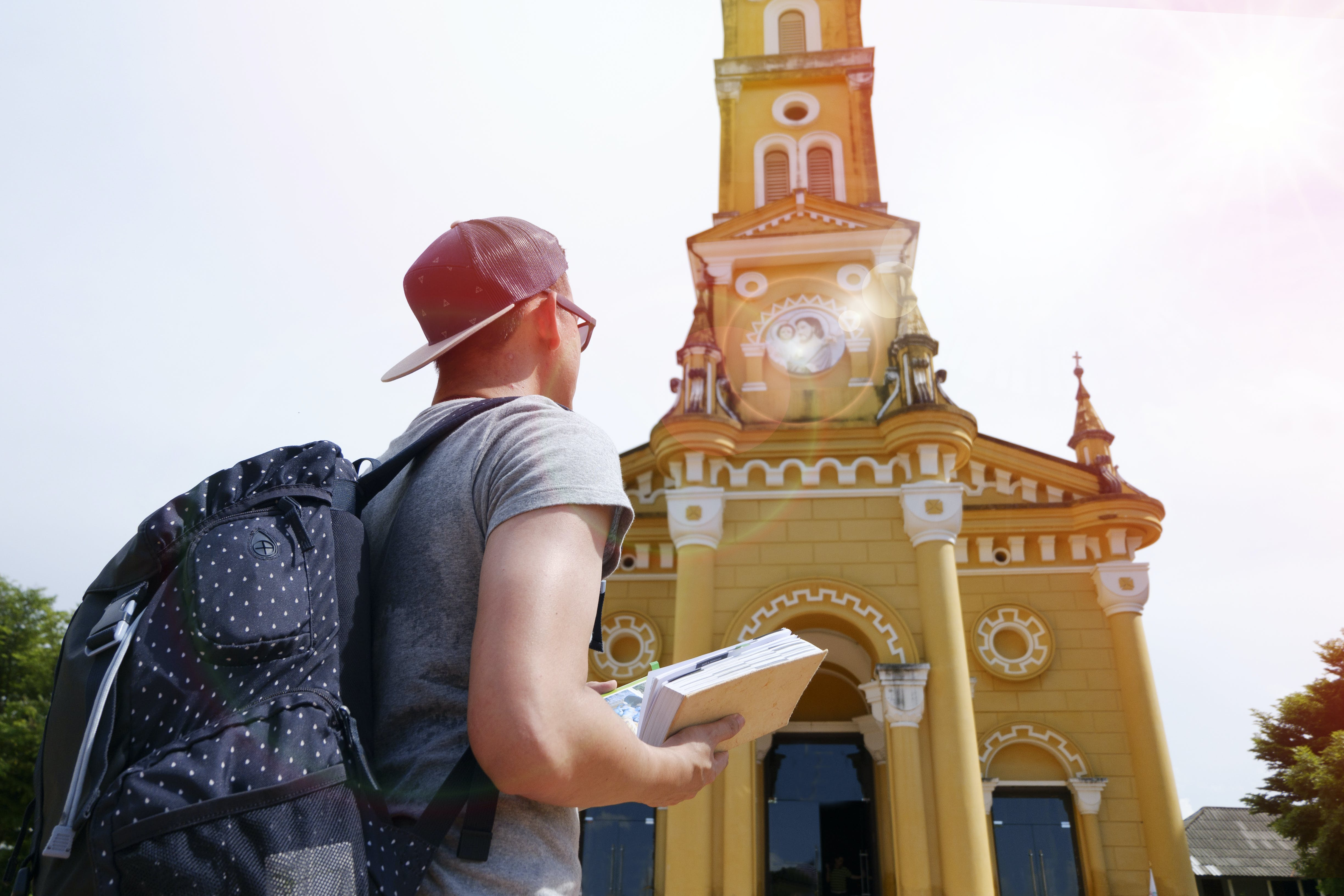 Man in Grey Top With Backpack Standing in Front of Cathedral