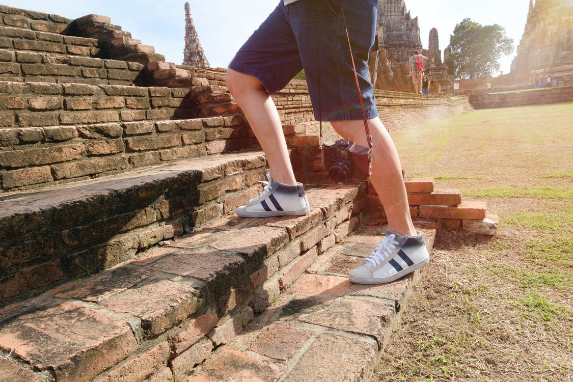 Person Wearing White-and-black Mid-rise Sneakers at Borobudur, Indonesia