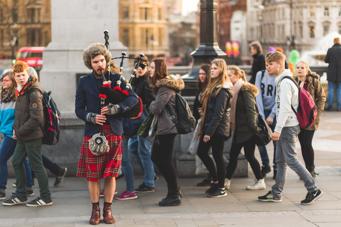 Person Using Bag Pipe Wind Instrument Near People Walking
