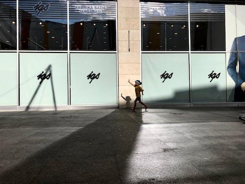 Woman in Yellow Shirt and Black Pants Walking on Sidewalk