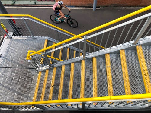 Person Riding Bicycle on Yellow and Gray Metal Railings