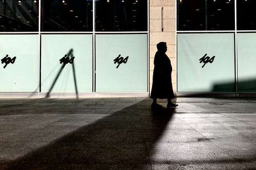 Silhouette of Woman Walking Beside Building