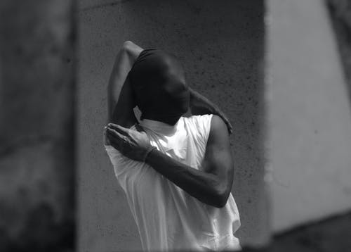 Gray scale Photo of Person in Sleeveless T-shirt and Covered Face