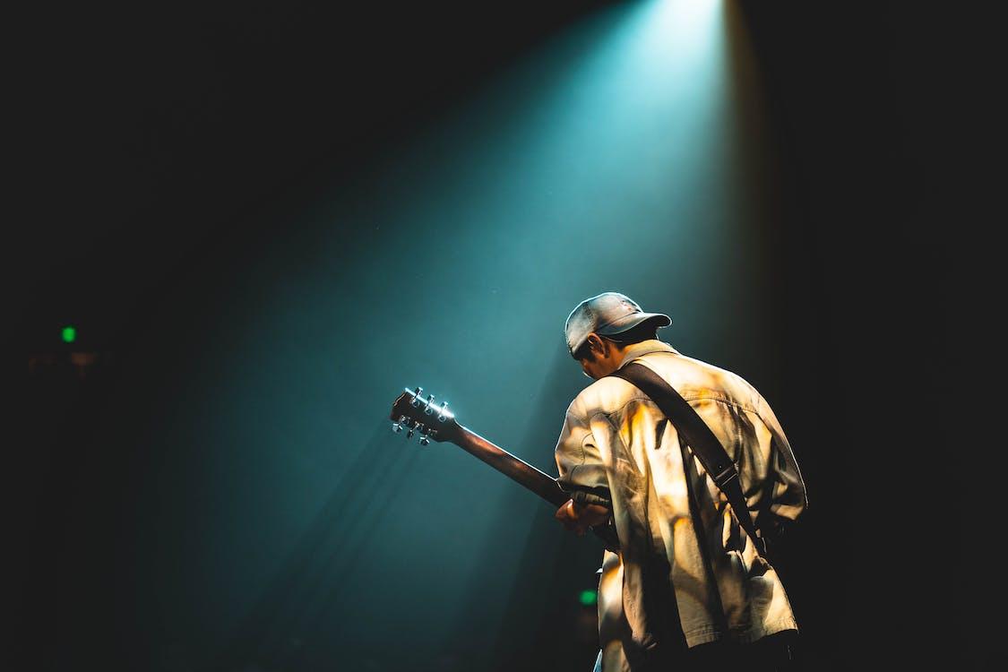 Photo of Man Playing Guitar