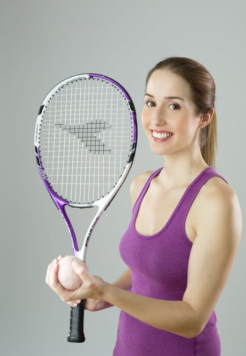 Woman Wearing Purple Tank Top Holding Purple and White Racket and Lawn Tennis Ball