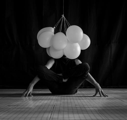 Grayscale Photo of Person in Front of Balloons