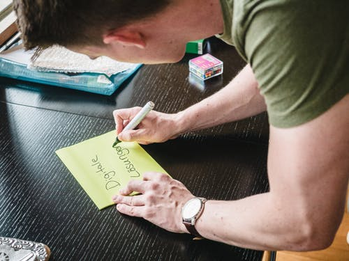 Man in Green T-shirt and Silver Watch Holding Yellow Sticky Notes