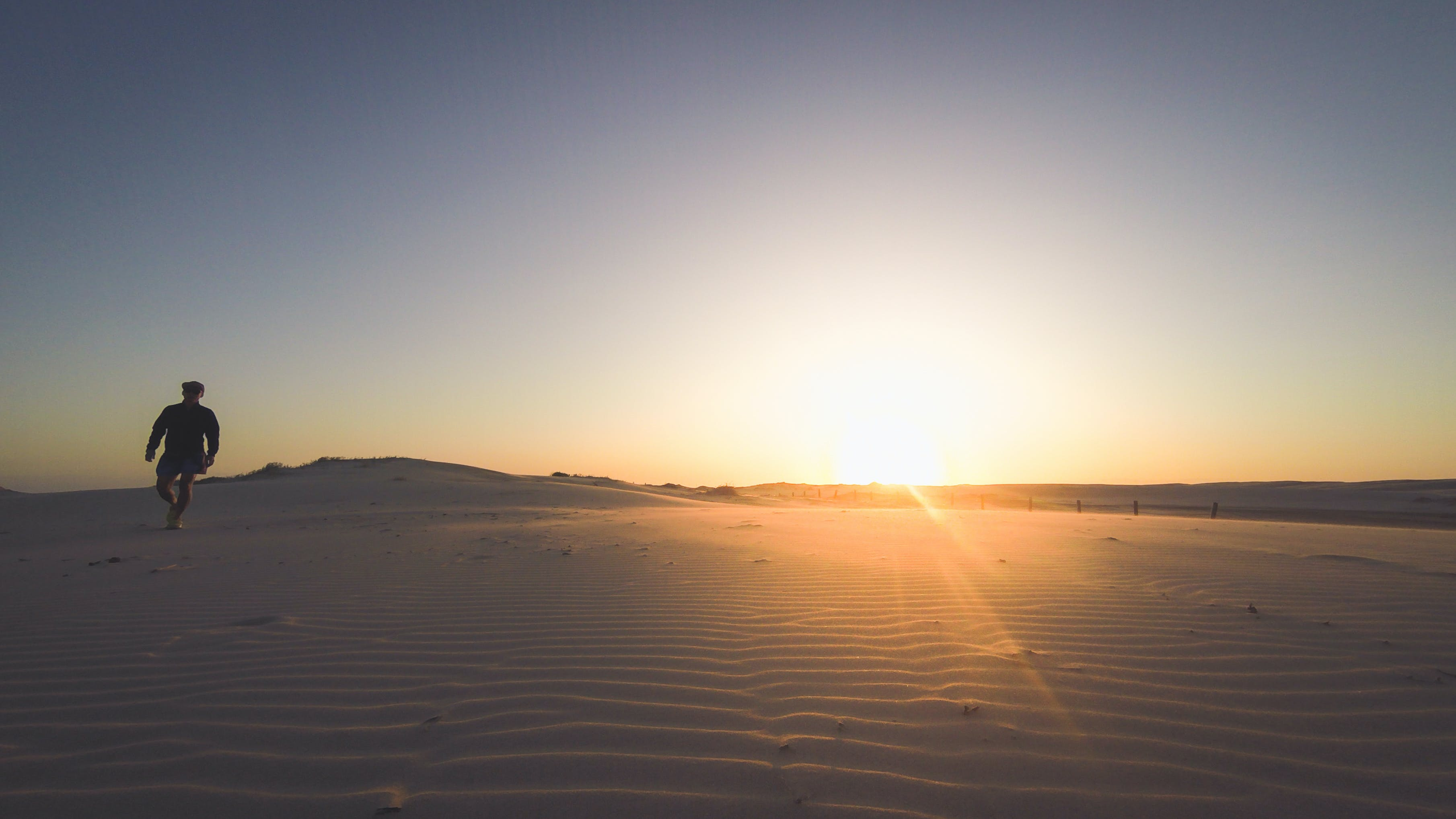 Person Standing on Desert during Sunset